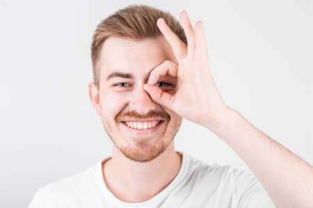 Positive funny male in casual clothes shows ok sign, laughs at camera, demonstrates that everything is fine.