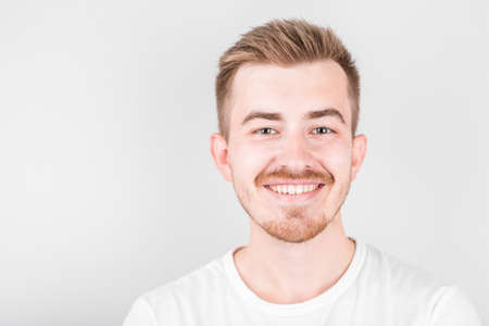 Confident young handsome man in white shirt smiling while standing against white background.