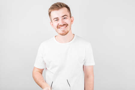 Image of optimistic positive young unshaved man in hat isolated over white wall background
