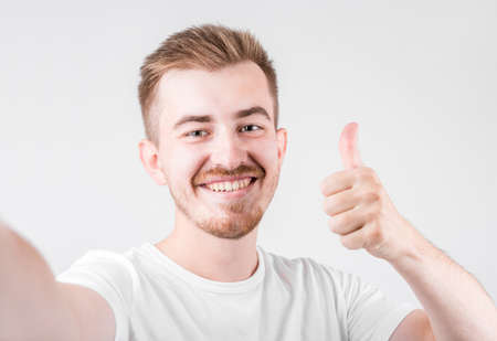 Photo of handsome man in casual t-shirt, smiling on camera with thumb up while taking selfie isolated over white background.