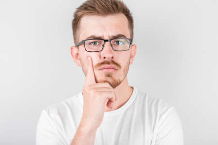 Pensive man in glasses isolated on gray white blank pose look forward at camera and touch chin lost on thoughts thinking planning future.