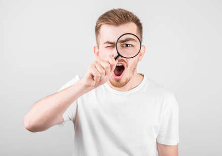 Shocked man looking in magnifier on gray background. Stockfoto