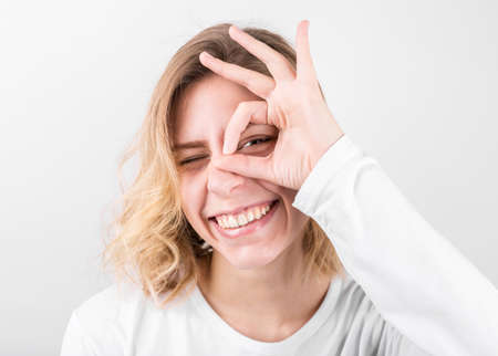 Positive funny female in casual clothes shows ok sign, laughs at camera, demonstrates that everything is fine