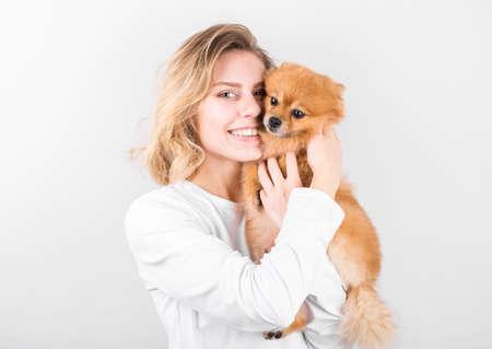 Pleased happy girl gets lovely puppy. Woman hugs Pomeranian spitz