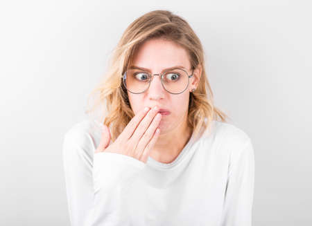 Young woman disgusted squeamishness over gray wall background. Stockfoto