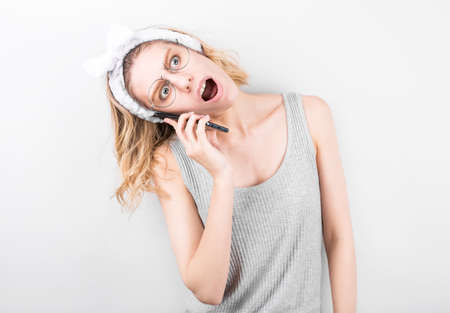 Portrait of a shocked young girl using mobile phone isolated over gray background.