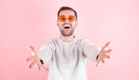 Come to me A portrait of a friendly kind man in a casual white spitshot, wearing bright glasses, stretching out his arms wide for free hugs and smiling happily, affable, about to hug. indoor studio shot isolated on pink background