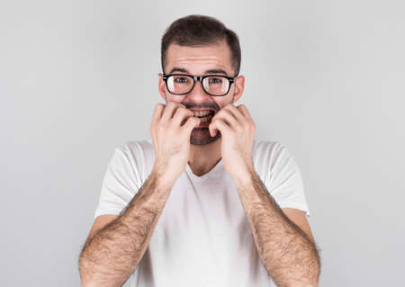 Young man covering mouth with hands and round eyes, wearing round eyeglasses, experiencing deep astonishment and fear, isolated on gray background