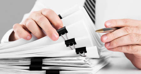 Businessman hands working in stacks of paper files for searching information on work desk home office, business concept.