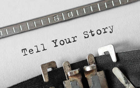 Text Tell Your Story typed on retro typewriter Imagens