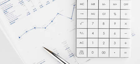 Financial charts and a calculator on the accountant's desk. Calculating profits, taxes, and paying employees salaries. Stock Photo