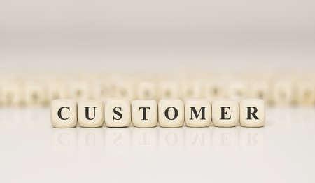 Word CUSTOMER written on wood block. Business concept