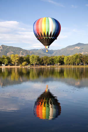 A hot air balloon rises above Prospect Lake during the Colorado Springs Balloon Classic.  Stock Photo - 7498713