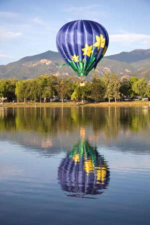 A hot air balloon rises above Prospect Lake during the Colorado Springs Balloon Classic.
