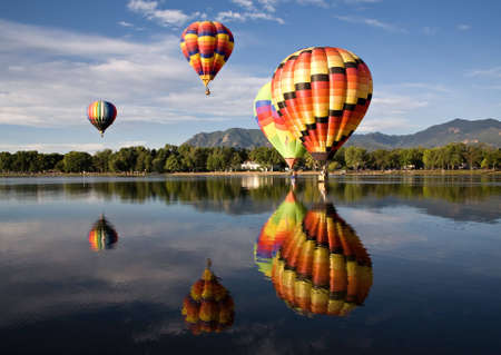 Colorful balloons are reflected in Prospect Lake during Colorado Springs Balloon Classic.