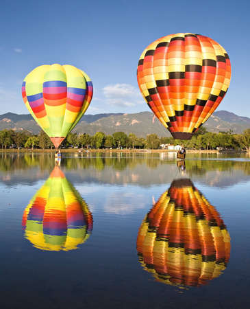 Colorful balloons are reflected in Prospect Lake during Colorado Springs Balloon Classic.  Stock Photo
