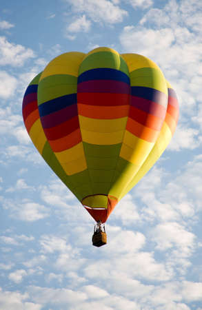 cloud drift: A colorful balloon rises against the beautiful cloudy sky during Colorado Springs Balloon Classic