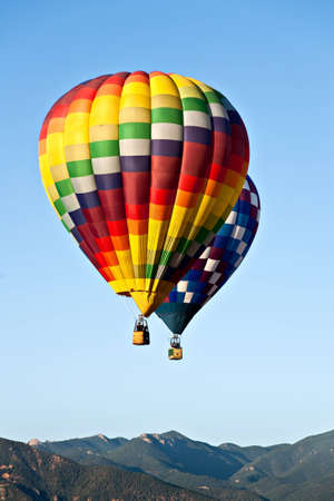 ascend: Two hot air balloons ascend over front range mountains during Colorado Springs Stock Photo
