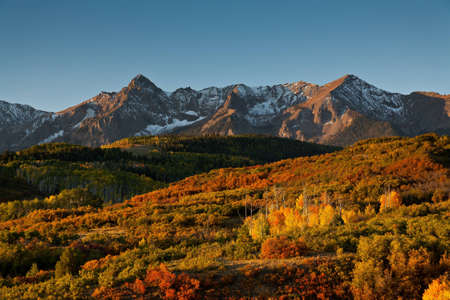 The rising sun illuminates Sneffles Range at Dallas Divide in Colorado photo