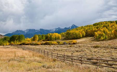san juans: A fence runs along a Colorado highway in the San Juan Mountains near Dallas Divide