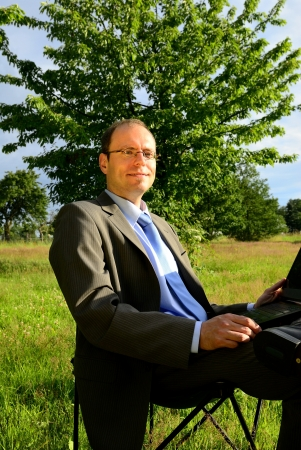 Green IT businessman working outdoor with laptop on green grass Stock Photo - 14156440