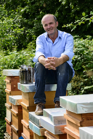 beekeeper with smoker sitting on beehives