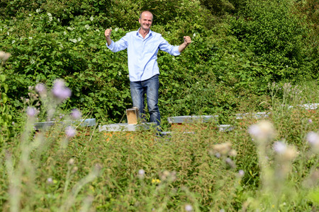 industriousness: Beekeeper standing on his hives