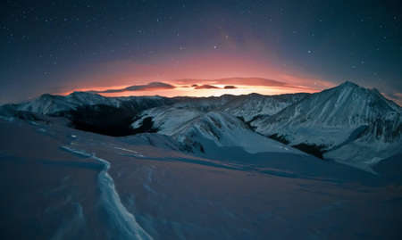 Light pollution glows with a certain beauty against the starry night sky.  This image was taken after a snowshoe trek above Loveland Pass, west of Denver, Colorado. photo
