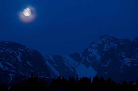A full moon sets in the early morning hours of late spring over the peaks of Rocky Mountain National Park.  This image was taken near the Storm Pass trailhead above Estes Park, Colorado. photo