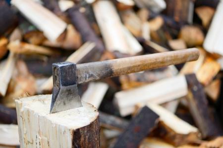 Oude bijl op een brandhout