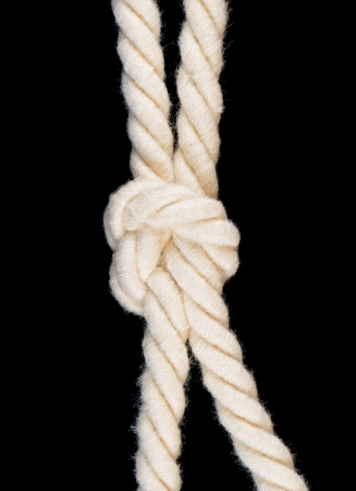 Rope with knot isolated on black background photo