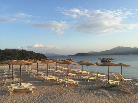 An empty beach with wooden umbrellas and lounge chairs, in Sardinia Italy
