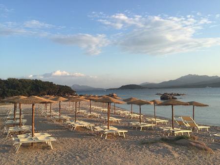 Ein leerer Strand mit hölzernen Regenschirmen und Klubsesseln, in Sardinien Italien Standard-Bild - 60618097