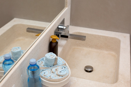 granite bathroom sink with hand soap, bottle water and towels