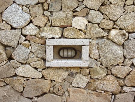 light fixture: A light fixture inside a granite rock fence Stock Photo