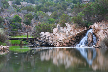 An old wooden bridge crossing to a waterfall at a pond in Sardinia, Italy.