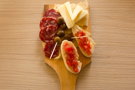 A mix of foods for appetizer, cheese, olives,bread and salami