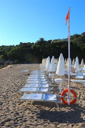 beach buoy: An empty beach with lifeguard buoy at sunrise in Sardinia Italy