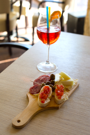 A mix of foods for appetizer, cheese, olives,bread and salami with a beverage