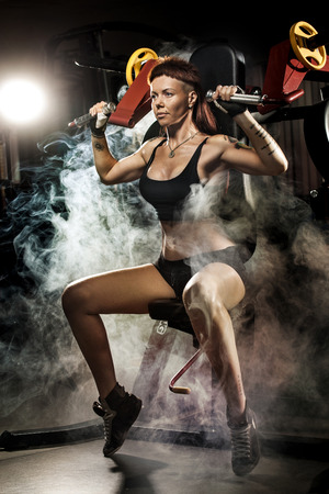 Strong woman at the gym doing exercises on a machine at fitness club photo