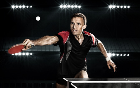 table tennis: Portrait Of Young Man Playing Tennis On Black Background with lights Stock Photo