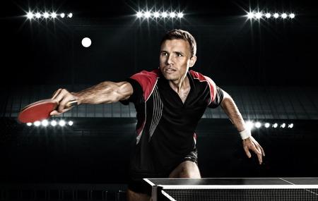 ping pong: Retrato de hombre joven que juega a tenis en el fondo Negro con luces Foto de archivo