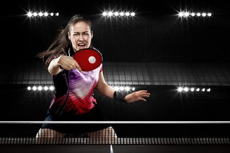 Retrato de la chica joven que juega a tenis en el fondo Negro con luces