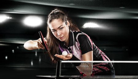 Portrait Of Young Woman Playing Tennis On Black Background with lights Standard-Bild