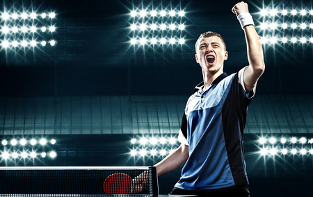tischtennis: Portrait des jungen Mannes feiern Flawless Victory in Tischtennis auf dunklem Hintergrund mit Lichtern Lizenzfreie Bilder