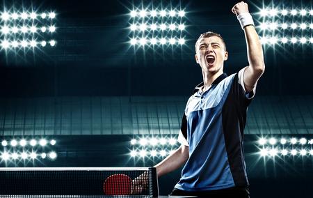ping pong: Retrato del hombre joven que celebra la victoria impecable en Mesa de ping pong en el fondo oscuro con luces