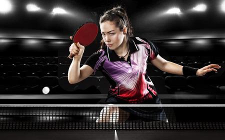 ping pong: Retrato de la chica joven que juega a tenis en el fondo Negro con luces
