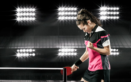 table tennis: Portrait Of Young Girl Celebrating Flawless Victory in Table Tennis On Dark Background with lights