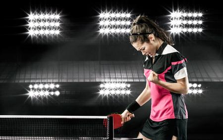 jugando tenis: Retrato de la chica joven que celebra la victoria impecable en Mesa de ping pong en el fondo oscuro con luces Foto de archivo