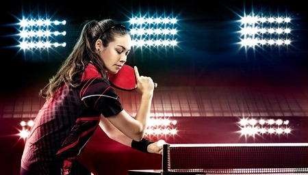 table tennis: Portrait Of Young Woman Playing Tennis On Black Background with lights Stock Photo